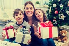 有坐在圣诞树前面的两个孩子的微笑的母亲为假日做准备 库存图片
