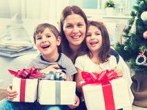 有坐在圣诞树前面的两个孩子的微笑的母亲为假日做准备 免版税图库摄影