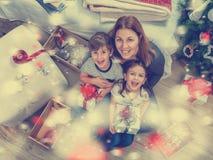 有坐在圣诞树前面的两个孩子的微笑的母亲为假日做准备 免版税库存图片