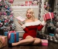 有坐在圣诞树附近的礼物的圣诞节女孩 作为加工好的圣诞老人妇女 库存照片