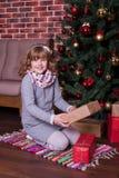 有坐在圣诞树附近的礼物的微笑的女孩 免版税库存图片