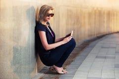 有坐在墙壁的片剂计算机的年轻时尚妇女 免版税库存照片