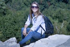 有坐在山顶部的背包的愉快的少妇 Tra 库存图片