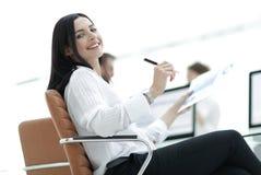 有坐在工作书桌的财政文件的微笑的女商人 免版税库存图片