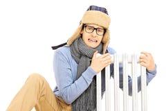 有坐在幅射器旁边的冬天帽子的变冷的年轻人 免版税库存图片