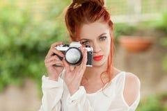 有坐在庭院里的红色头发的美丽的少妇拍与照相机的照片 免版税库存照片