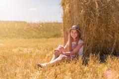 有坐在成熟麦子的领域的一个干草堆下的长的金发的年轻愉快的女孩 库存图片