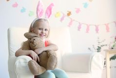 有坐在扶手椅子的兔宝宝耳朵和爱拥抱玩具的逗人喜爱的小女孩 免版税库存图片