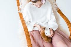 有坐在摇椅的逗人喜爱的毛茸的兔宝宝的女孩 库存图片