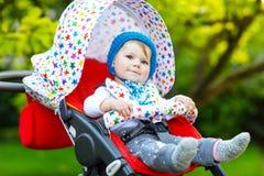 有坐在摇篮车或婴儿推车和等待妈妈的蓝色温暖的帽子的逗人喜爱的健康矮小的美丽的女婴 ?? 免版税库存照片