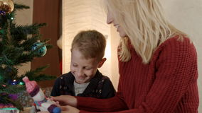 有坐在新年树和戏剧下的母亲的愉快的儿子与雪人 股票录像