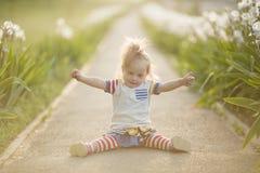 有坐在日落太阳的唐氏综合症的滑稽的女孩 免版税库存照片