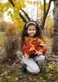 有坐在有花楸浆果花束的秋天森林里的黑暗的卷发的逗人喜爱的女孩  免版税图库摄影
