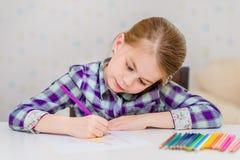 有坐在桌上和画与多彩多姿的铅笔的金发的美丽的沉思小女孩 免版税库存照片