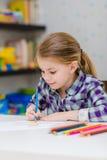 有坐在桌上和画与多彩多姿的铅笔的金发的逗人喜爱的微笑的小女孩 免版税库存照片