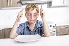 有坐在桌上的乏味脾气坏的表示的小男孩 库存图片