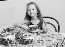 有坐在桌上的长的金发的一个美丽的小女孩 图库摄影