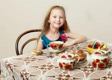 有坐在桌上的长的金发的一个美丽的小女孩 免版税库存照片