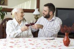 有坐在桌和多士上的孙子的祖母拿着一杯红葡萄酒 图库摄影