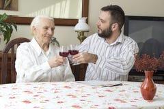 有坐在桌和多士上的孙子的祖母拿着一杯红葡萄酒 免版税图库摄影