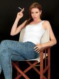 有坐在椅子的态度的美丽的少妇拿着未点燃的香烟 库存照片