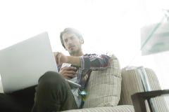 有坐在椅子的智能手机的照片年轻人 在模糊的背景 免版税库存照片