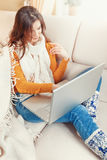 有坐在沙发温暖的格子花呢披肩的膝上型计算机的女孩 库存照片