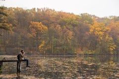 有坐在河岸和看美好的小阳春风景的背包的年轻女性远足者 图库摄影
