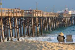 有坐在海滩睡椅的帽子的一个人 免版税库存照片