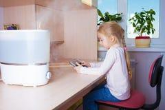 有坐在润湿器附近的片剂个人计算机的小女孩 免版税库存图片