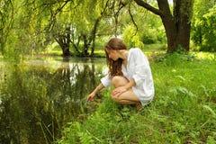 有坐在湖附近的长的头发的女孩在树荫下 免版税图库摄影