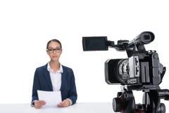 有坐在照相机前面的纸的可爱的女性新闻广播员, 库存图片