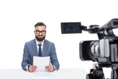 有坐在照相机前面的纸的微笑的男性新闻广播员, 库存照片
