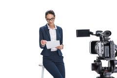 有坐在照相机前面的纸的美丽的微笑的女性新闻广播员, 图库摄影