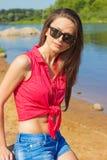 有坐在牛仔布的长的黑发佩带的太阳镜的性感的美丽的女孩在海滩短缺在水附近在一个晴天 免版税库存照片