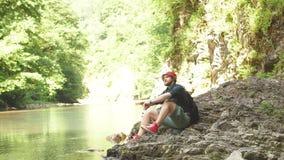 有坐在狂放的夏天木头的湖附近的背包的旅游人 远征 股票录像