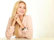 有坐在白色桌上的干净的面孔的年轻自然妇女倾斜在她的手肘,在背景 免版税库存图片
