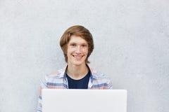 有坐在白色背景的引人注目的外观的微笑的十几岁的男孩使用观看的影片或打的比赛膝上型计算机 col 库存照片