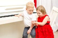 有坐在白色钢琴附近的女孩的男孩 库存照片