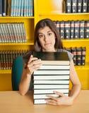 有坐在的被堆积的书的迷茫的学生 库存图片