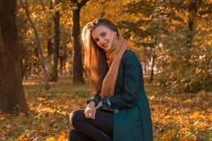 有坐在秋天公园和微笑的长的头发的年轻迷人的女孩 库存图片