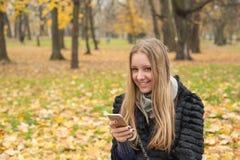 有坐在秋天的公园的长的头发的青少年的女孩与智能手机 库存照片