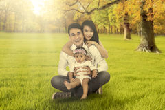 有坐在秋天领域的女儿的父母 库存图片