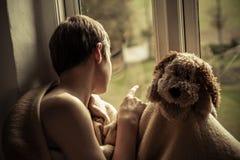 有坐在窗口基石的毯子和玩具的男孩 免版税图库摄影
