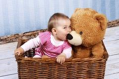 有坐在篮子的玩具熊的小孩 库存照片