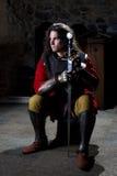 有坐在老教会里的剑的中世纪战士看  免版税库存图片