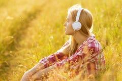 有坐在草的耳机的女孩 免版税库存照片