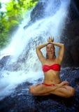 有坐在莲花姿势的适合身体实践的瑜伽湿下面热带天堂瀑布小河的年轻可爱和愉快的妇女 库存照片