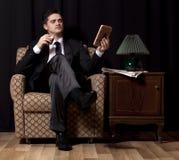 有坐在葡萄酒扶手椅子的酒精的人 免版税库存图片