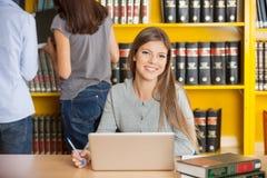 有坐在表上的膝上型计算机的妇女在学院 免版税库存图片